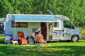 Class C Motorhome parked at an RV Resort. Woman on Patio Chairs with dog under an awning