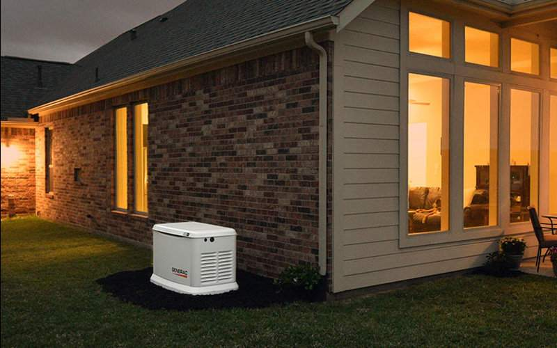 A Generac Generator Installed Next to a Home with Lights On