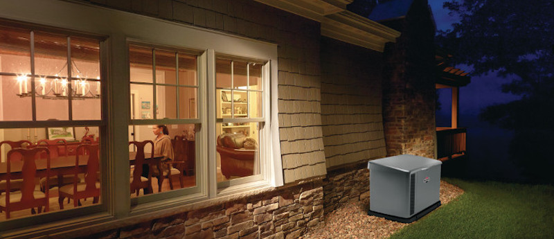 Briggs and Stratton 17kW Home Standby Generator with Whole House Automatic Transfer Switch Outside a House with lights on and comfortable homeowners inside.
