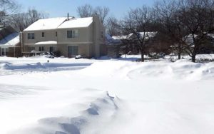 A Suburban Home surrounded by deep snow after a winter storm