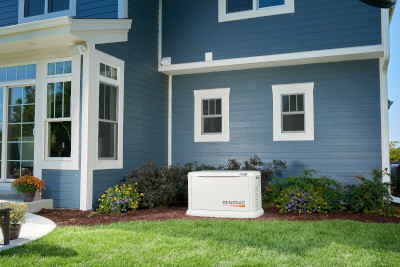 A Generac Guardian Generator Supplies Emergency Power to a Blue Two Story Home