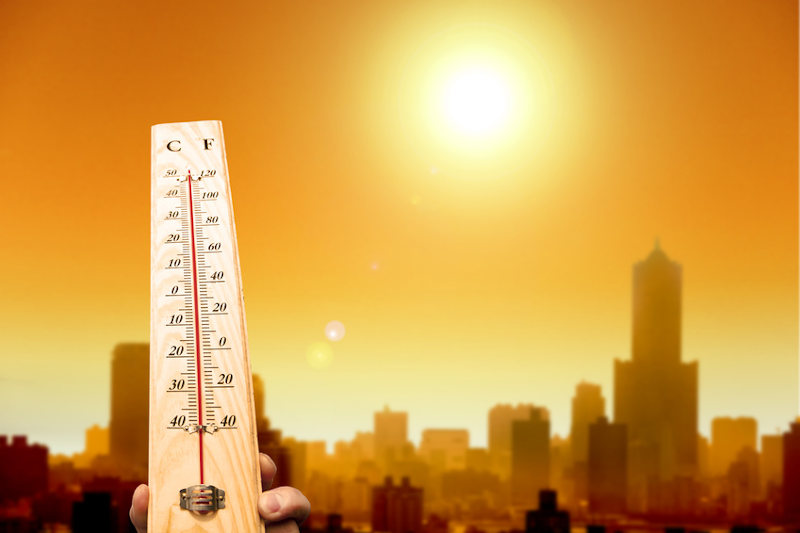 A thermometer with high temperatures against a city and overhead sun