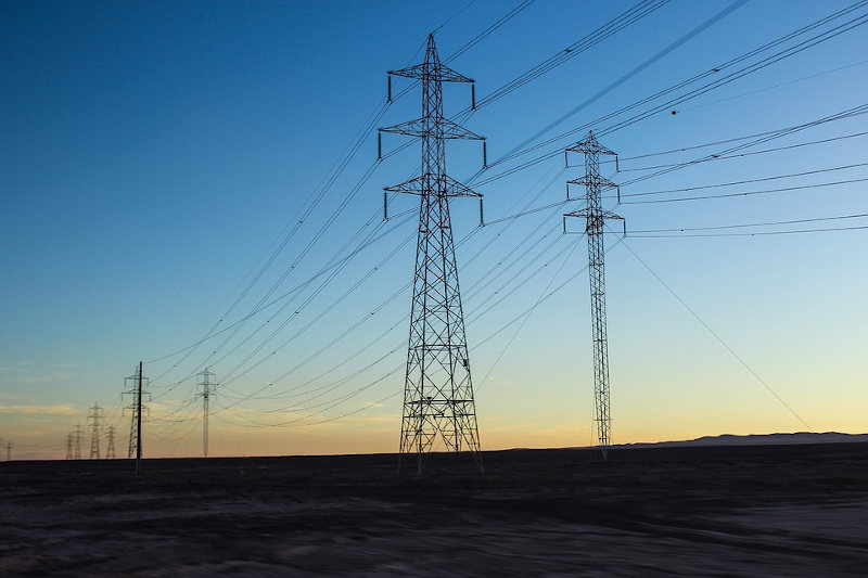 Transmission lines and towers against a backdrop of fading daylight