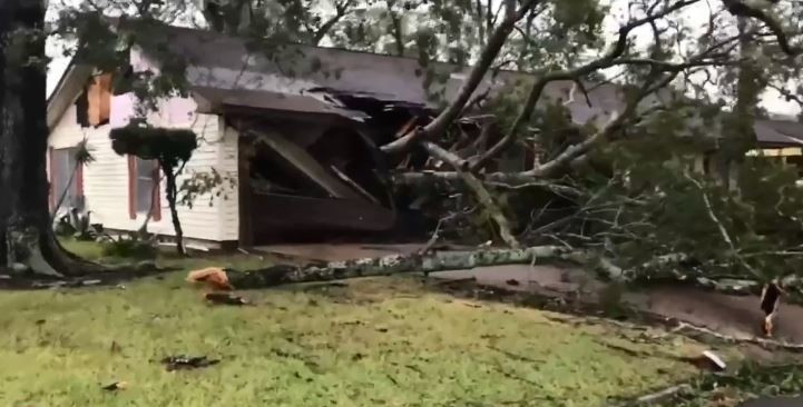 A fallen tree shatters the roof and front portion of a home during hurricane laura