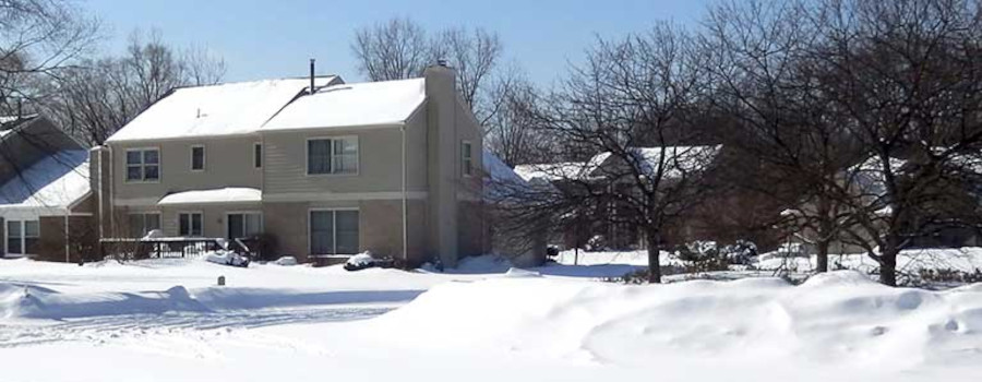 A suburban neighborhood after heavy snowfall experiences a power outage. A single home with a whole home backup generator has power from the generator.